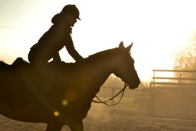 Heidi hevosensa kanssa auringon laskiessa.